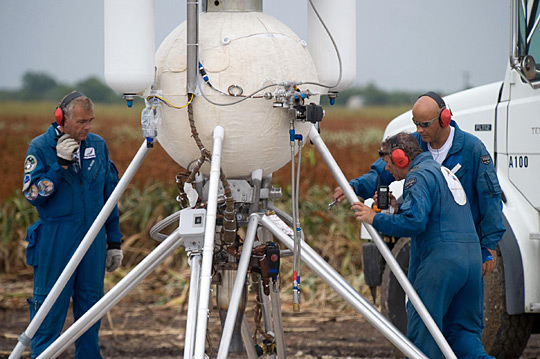 Armadillo Aerospace technicians on the launch pad performing a vehicle inspection.