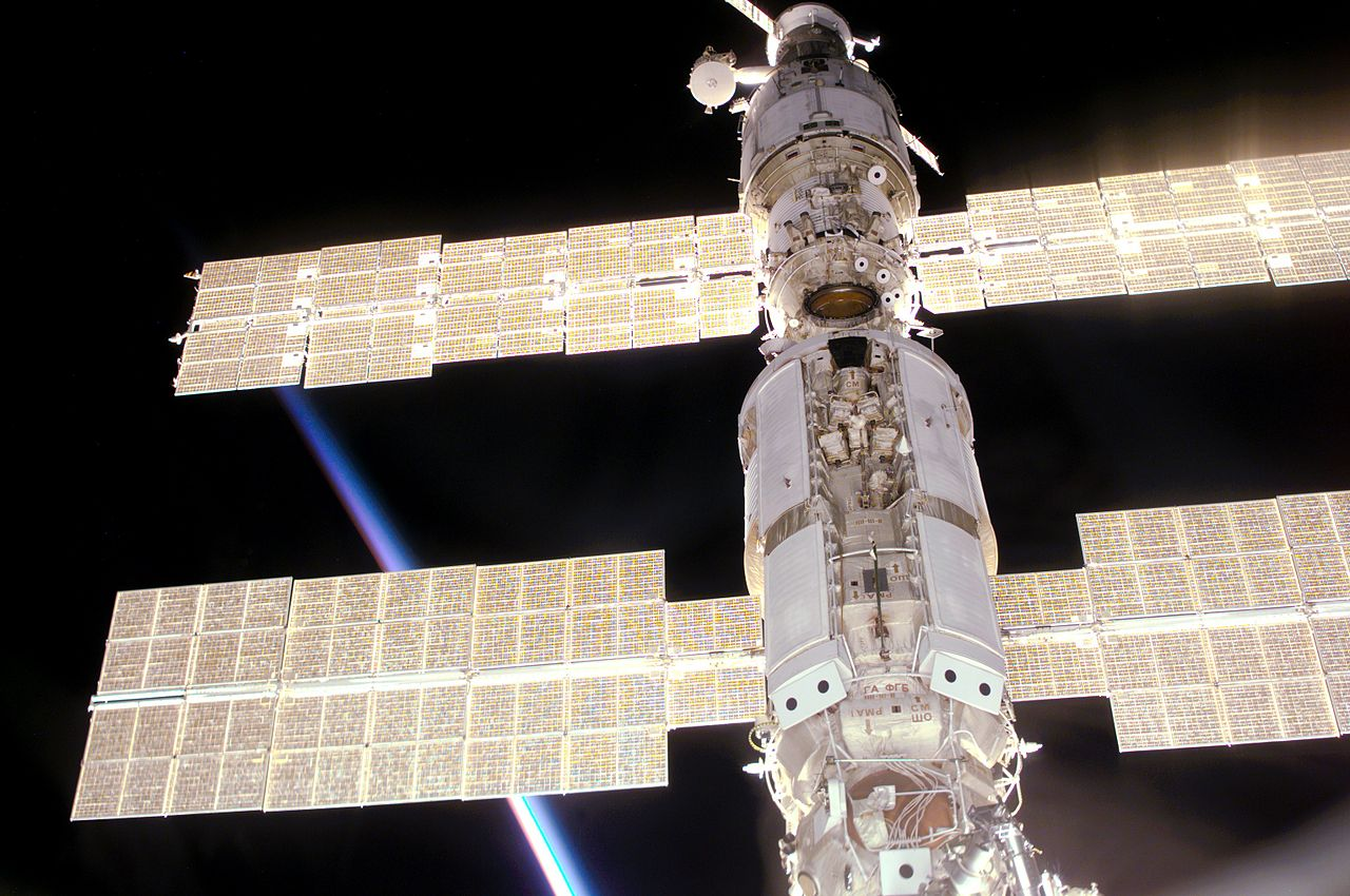 Solar arrays of space station modules backlit by the Sun