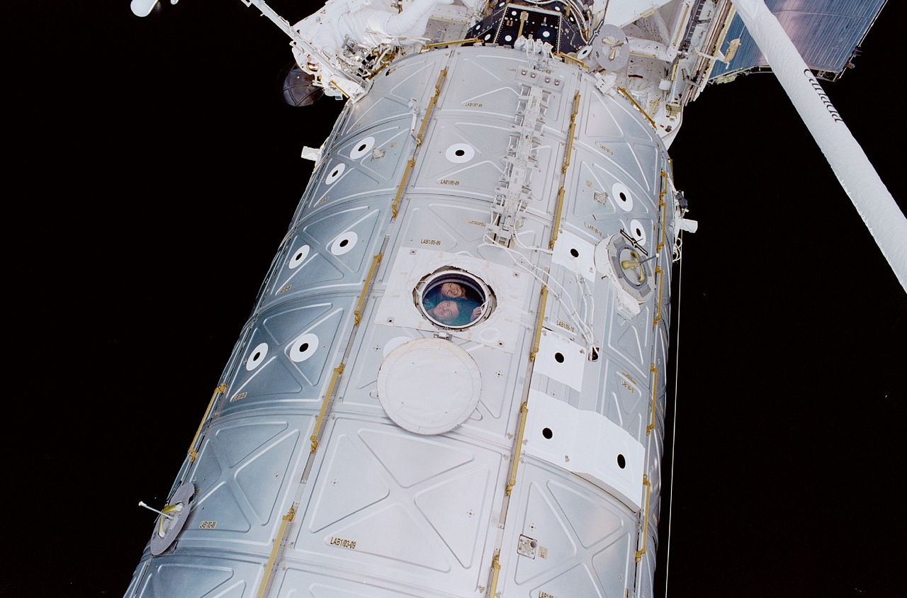 Astronauts peer out of Destiny Laboratory, 2001