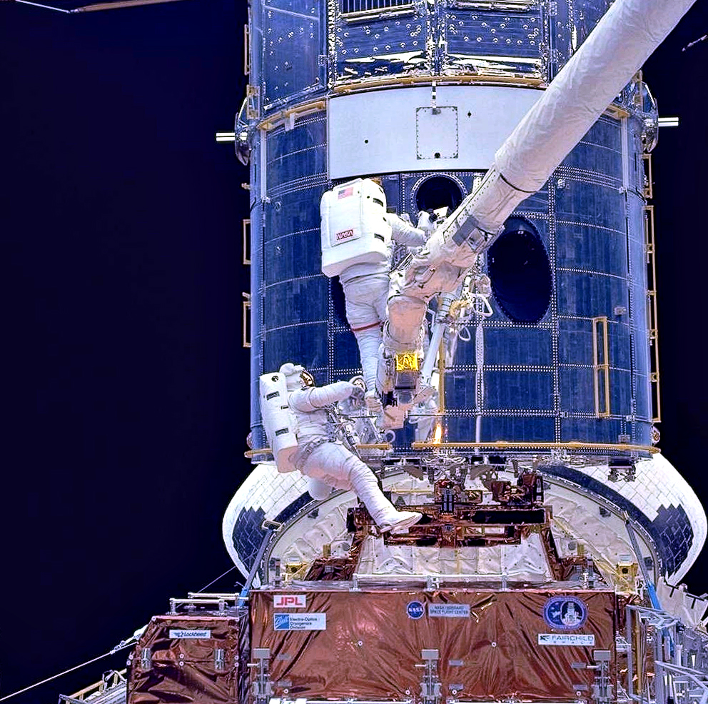Astronauts Thomas D. Akers and Kathryn C. Thornton install corrective optics on the Hubble Space Telescope during STS-61