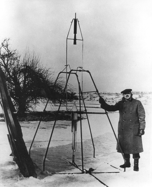 Robert H. Goddard, bundled against the cold New England weather of March 16, 1926, holds the launching frame of his most notable invention — the first liquid rocket.