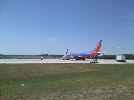 A Southwest Airlines 737-700 with a military charter on the apron.
