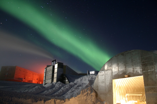 A photo of the station in the night. The new station can be seen at the far left, the electric power plant is in the center, and the old vehicle mechanic's garage in the lower right. The green light in the sky is part of the aurora australis.