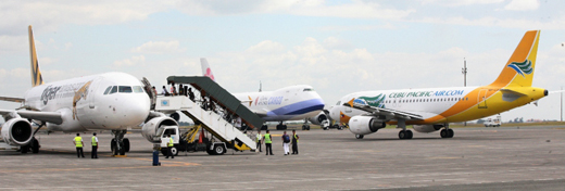 A Cebu Pacific plane taxies between two aircraft as passengers board a Tiger Airways airplane. In the background is a China Airlines Cargo Boeing 747.