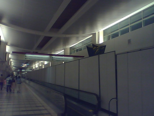 Semi-permanent barriers separating arrival and departure passengers.