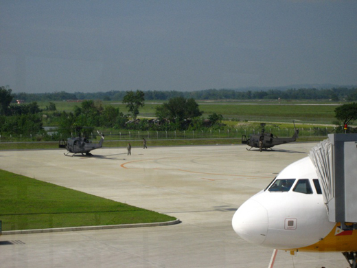 A Cebu Pacific aircraft and two military helicopters parked at the Iloilo International Airport apron