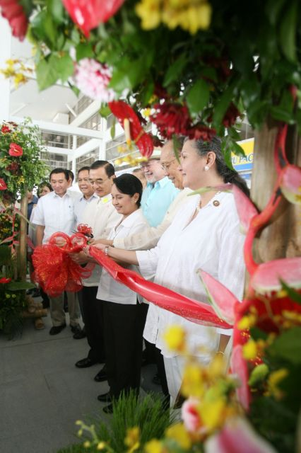 Accompanied by national and local officials, President Gloria Macapagal-Arroyo cuts the ribbon at the airport ribbon cutting ceremony on June 13, 2007.