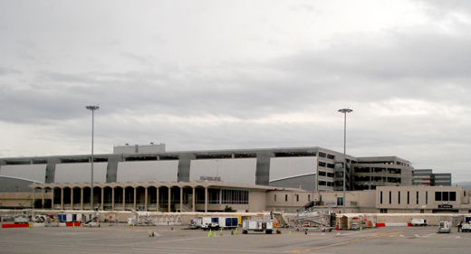 Terminal C with its dark windows in the foreground, with the new parking structure behind it in early 2010