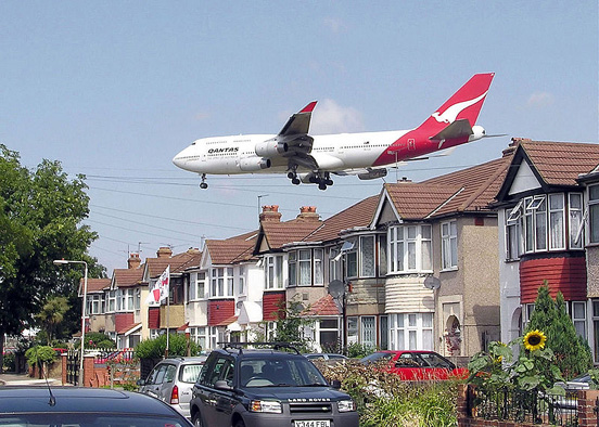 A landing Qantas Boeing 747-400 passes close to houses on the boundary of London Heathrow Airport, England