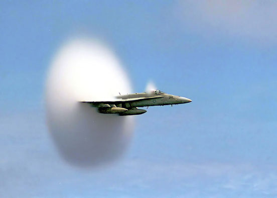 U.S. Navy F/A-18 breaking the sound barrier. The white halo is formed by condensed water droplets which are thought to result from a drop in air pressure around the aircraft (see Prandtl-Glauert Singularity).