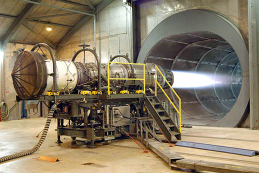 A Pratt & Whitney F100 turbofan engine for the F-15 Eagle and the F-16 Falcon being tested in the hush house at Robins Air Force Base, Georgia, USA. The tunnel behind the engine muffles noise and allows exhaust to escape