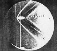 Shadowgraph of the detached shock on a bullet in supersonic flight, published by Ernst Mach in 1887.