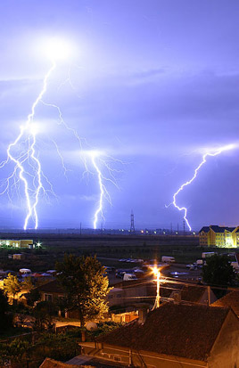 Lightning is an example of plasma present at Earth's surface. Typically, lightning discharges 30,000 amperes, at up to 100 million volts, and emits light, radio waves, x-rays and even gamma rays. Plasma temperatures in lightning can approach ~28,000 Kelvin (~27,700°C) and electron densities may exceed 10/m³.