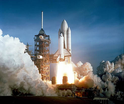 STS-1 at liftoff. The External Tank was painted white for the first two Space Shuttle launches. From STS-3 on, it was left unpainted.