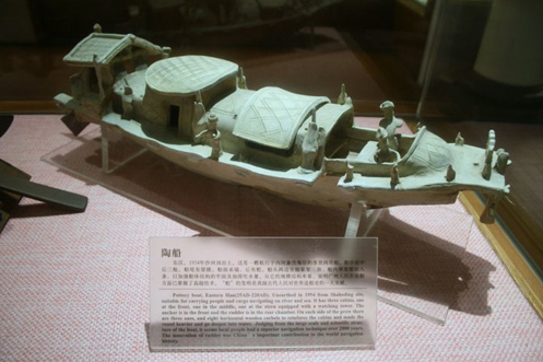 An Eastern Han (25–220 AD) Chinese pottery boat fit for riverine and maritime sea travel, with an anchor at the bow, a steering rudder at the stern, roofed compartments with windows and doors, and miniature sailors.