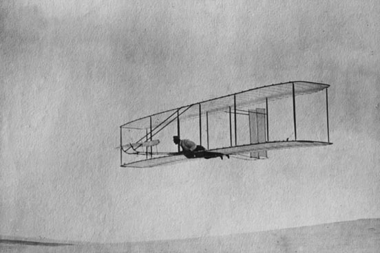 The 1902 Wright Glider(Wilbur piloting) on one of its early test flights before replacement of the fixed double vertical rudder with a single steerable rudder.