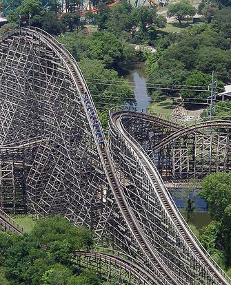 The cars of a roller coaster reach their maximum kinetic energy when at the bottom of their path. When they start rising, the kinetic energy begins to be converted to gravitational potential energy. The sum of kinetic and potential energy in the system remains constant, assuming negligible losses to friction.