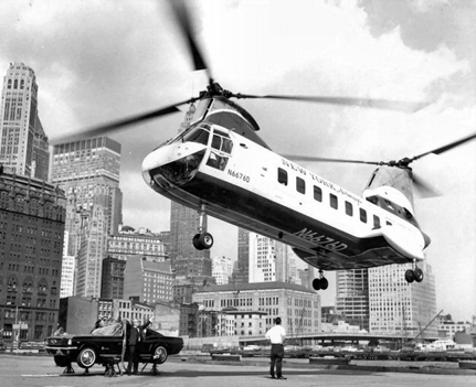 Taken at the West 30th Street Heliport, New York Airways N6676D is hooked to a Ford Mustang for publicity stunt. The Mustang was flown around Manhattan by the BV 107-II.
