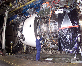 Mechanic working on a Rolls Royce Trent 900 engine during testing. The Trent is a typical type of high bypass turbofan used in wide-body airliners.