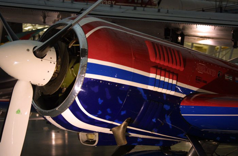 A Sukhoi Su-26 with red, blue, and purple cowling. Displayed in the National Air and Space Museum of the Smithsonian Institution in Washington, D.C.