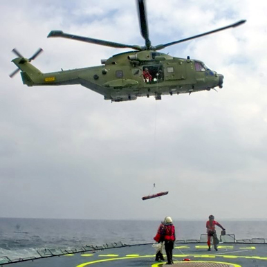 A Royal Danish Air Force AW101 hoisting from a ship's deck