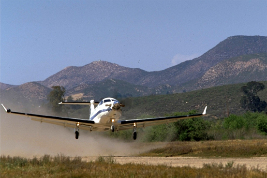 Pilatus PC-12 taking off from short, unimproved airfield