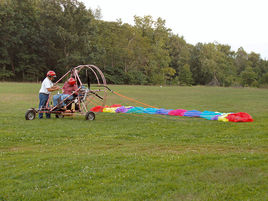 A powered parachute with its wing laid out in preparation for takeoff.