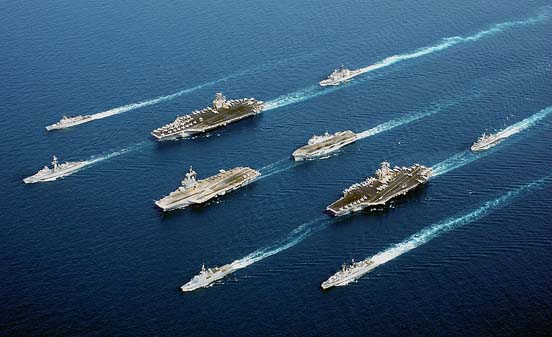 Four modern aircraft carriers of various types—USS John C. Stennis, FS Charles de Gaulle, HMS Ocean and USS John F. Kennedy—and escort vessels on operations in 2002. The ships are sailing much closer together than they would during combat operations.
