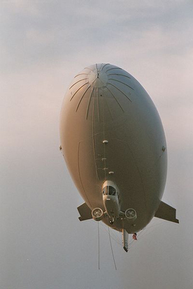 A modern blimp from Airship Management Services showing a strengthened nose, ducted fans attached to the gondola under the hull, and cable-braced fins at the tail