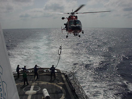 Raising a hose from ship to an HH-65