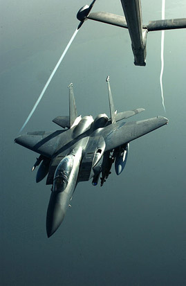 An F-15E Strike Eagle disengages from a KC-10 Extender, using a boom with an He 162 style of control surface