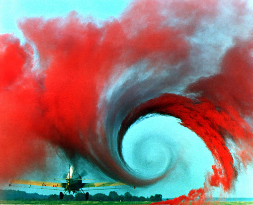 A vortex is created by the passage of an aircraft wing, revealed by smoke. Vortices are one of the many phenomena associated to the study of aerodynamics. The equations of aerodynamics show that the vortex is created by the difference in pressure between the upper and lower surface of the wing. At the end of the wing, the lower surface effectively tries to 'reach over' to the low pressure side, creating rotation and the vortex.