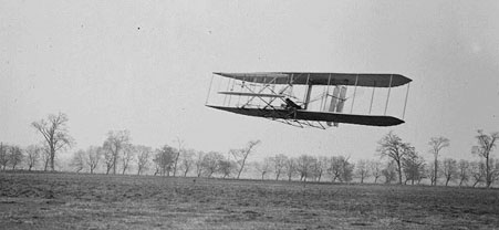 Orville in flight over Huffman Prairie in Wright Flyer II. Flight #85, approximately 1,760 feet (536 m) in 40 1/5 seconds, November 16, 1904.