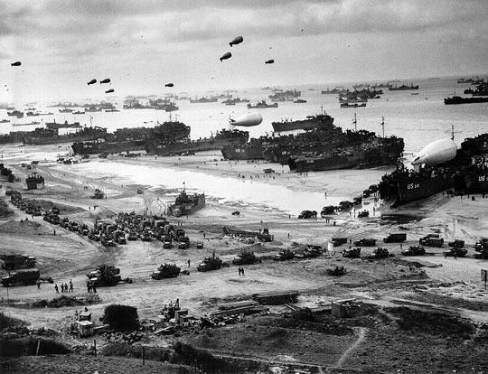 Landing ships putting cargo ashore on one of the invasion beaches during the Battle of Normandy. Note the barrage balloons.
