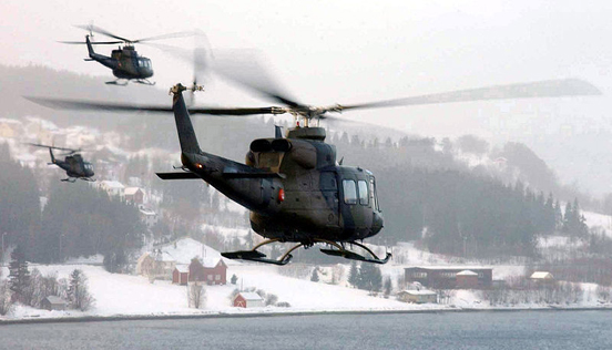 A group of Norwegian Bell 412 helicopters take part in a military exercise.