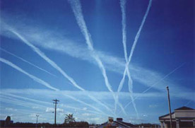 Water vapor contrails left by high-altitude jet airliners. These may contribute to cirrus cloud formation.
