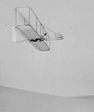 Wilbur Wright pilots the 1902 glider over the Kill Devil Hills, October 10, 1902. The single rear rudder is steerable; it replaced the original fixed double rudder.