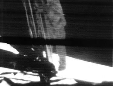 A mounted slowscan TV camera shows Neil Armstrong as he climbs down the ladder to surface