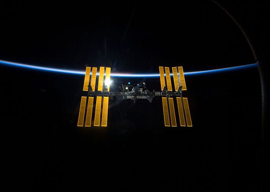 The ISS against the blackness of space and the thin line of Earth's atmosphere, taken from the Space Shuttle Discovery as the two spacecraft begin their separation.