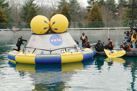 NASA and Department of Defense personnel familiarize themselves with a Navy-built, 18,000-pound Orion mock-up in a test pool at the Naval Surface Warfare Center's Carderock Division in West Bethesda, Md.