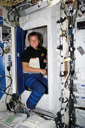 Astronaut Peggy Whitson in the doorway of a sleeping rack in the Destiny laboratory