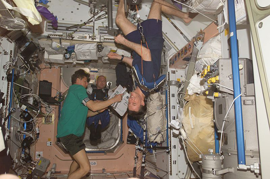 Astronauts on the ISS in weightless conditions. Michael Foale can be seen exercising in the foreground.
