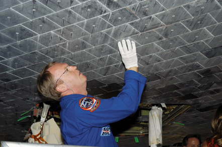 Astronaut Andrew S. W. Thomas takes a close look at TPS tiles underneath Space Shuttle Atlantis.