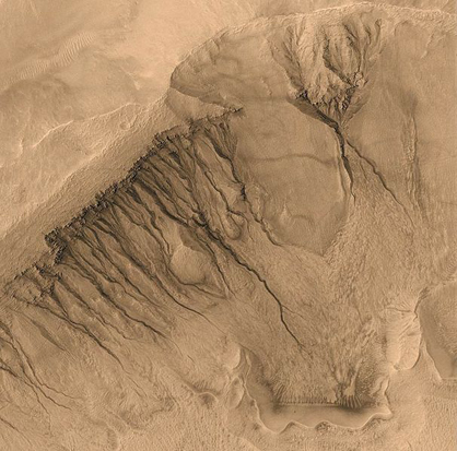 This image taken by Mars Global Surveyor spans a region about 1,500 m (4,921 ft) across, showing gullies on the walls of Newton Basin in Sirenum Terra. Similar channels on Earth are formed by flowing water, but on Mars the temperature is normally too cold and the atmosphere too thin to sustain liquid water. Nevertheless, many scientists hypothesize that liquid groundwater can sometimes surface on Mars, erode gullies and channels, and pool at the bottom before freezing and evaporating.