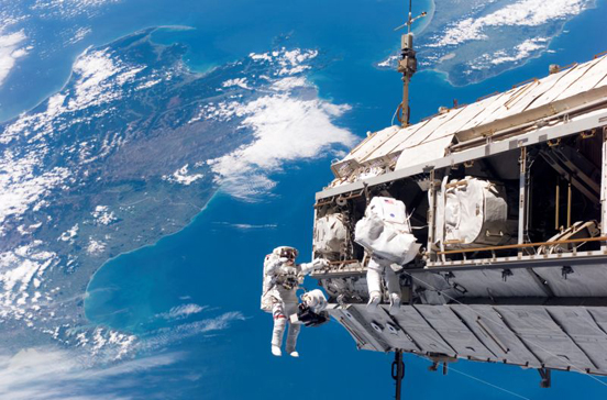 Backdropped by a colorful Earth, astronaut Robert L. Curbeam, Jr. (left) and European Space Agency (ESA) astronaut Christer Fuglesang, both STS-116 mission specialists, participate in an EVA